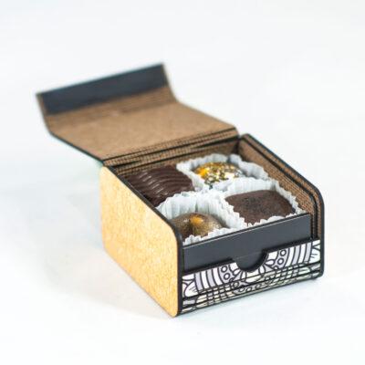 caja de madera que contiene bombones rellenos con patrón impreso inspirado en culturas mesoamericanas.