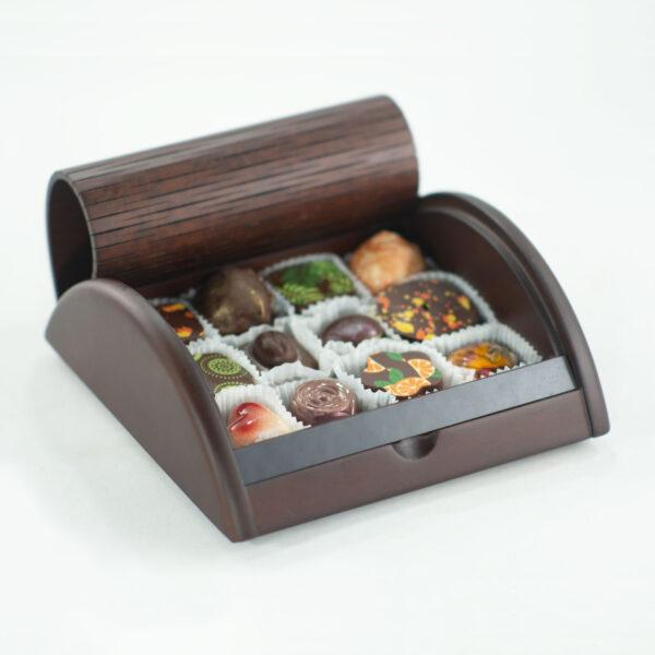 caja de madera estilo roll top abierta enseñando bombones de chocolate